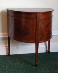 Lot 137: Miniature half moon cross banded drawing room/occasional table, on tapered leg  est. €600/800