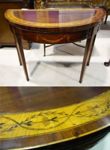 Lot 114: A Fine Quality, Irish, Georgian, Half Moon, Fold Over Card Table, Mahogany with Satinwood Panel and Carved Floral Details, with Marquetry Inlaid Honeysuckle to the tapered Legs est. €2000/3000