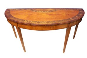 "A LARGE IRISH SATINWOOD AND MARQUETRY INLAID, DEMI LUNE, SIDE TABLE, by William Moore of Dublin, the semi elliptical top whose border is decorated with oval floral panels, and a large demi-medallion floral centre panel, with inlaid satinwood, sycamore and tulipwood, raised on tapering legs with an inlaid fluted freize, 64""x32""x25"" approx - est 15,000-20,000 Eur"