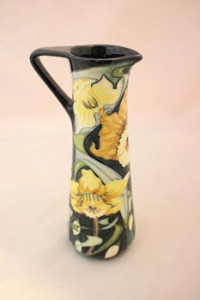 Lot 34: A 2003 MOORCROFT ARCTIC GOLD JUG/DAFFODIL JUG, RACHEL BISHOP designed, it is decorated with stylised daffodils on a dark background glaze, of shape number JU3, limited edition, numbered 121/250, with made in Stoke-on-Trent, England stamp, 2003, and signed by Rachel Bishop