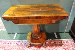 Lot 79: A ROSEWOOD FOLD OVER CARD TABLE, raised on an octagonal rounded column, with a circular base and terminating with four fluted and scroll tipped feet
