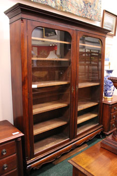 A TWO DOOR GLAZED BOOKCASE, raised on claw and ball cabriole leg
