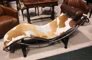 AN LC4 STYLE CHAISE LONGUE with hide seat cover and leather head