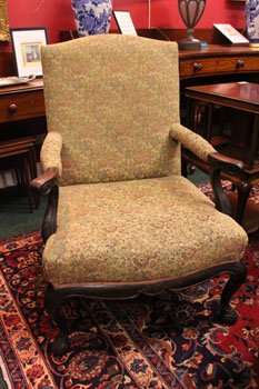 A LATE 19TH CENTURY ARMCHAIR, with scroll tipped feet, on cabrio